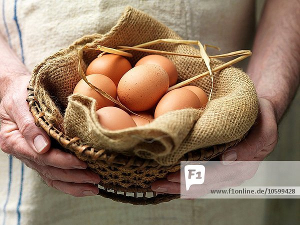 Senior woman holding eggs in vintage cloth and basket