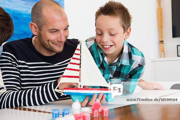Mittlerer Erwachsener Mann und Sohn bewundern gemaltes Spielzeugboot am Küchentisch