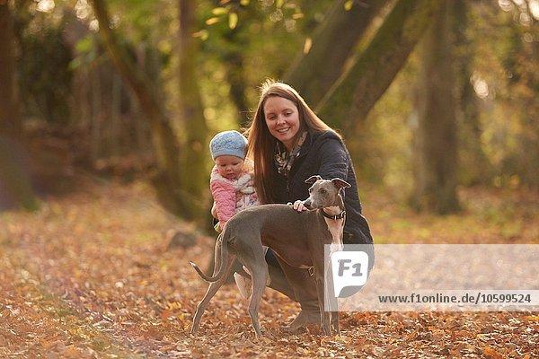Mittlere erwachsene Frau und kleine Tochter streichelnder Hund im Herbstpark