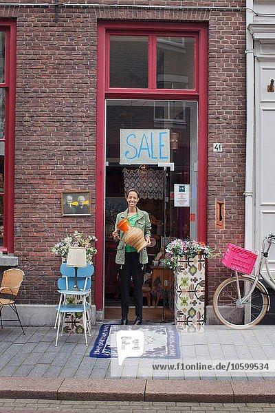 Porträt einer jungen Kundin vor dem Vintage-Shop