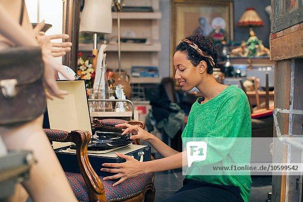 Junge Frau spielt Vinylplatten im Vintage-Shop Junge Frau spielt Vinylplatten im Vintage-Shop
