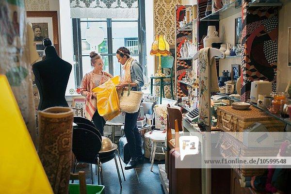 Junge Kundin beim Anblick der gelben Decke im Vintage-Shop