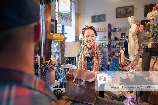 Glückliche junge Kundin beim Kauf im Vintage-Shop