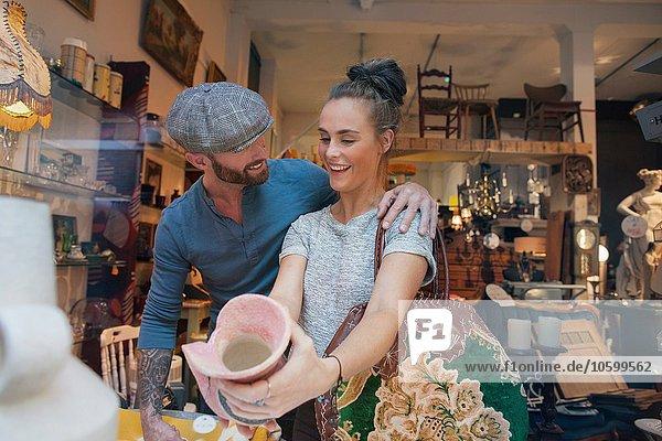 Junge Frau mit rosa Vase im Vintage-Shop