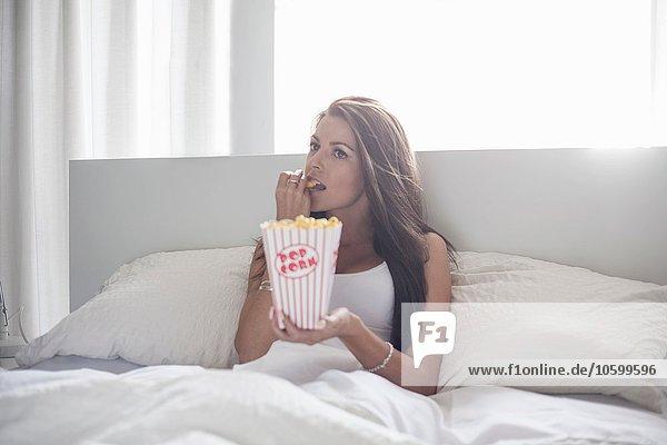 Junge Frau sitzt im Bett und isst Popcorn.