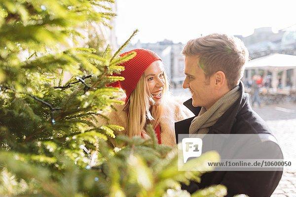Romantisches junges Paar neben dem Weihnachtsbaum in Covent Garden  London  UK Romantisches junges Paar neben dem Weihnachtsbaum in Covent Garden, London, UK
