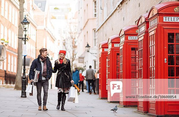 Young shopping couple strolling past red phone boxes  London  UK