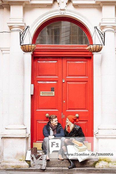 Young shopping couple taking a break on doorstep  London  UK
