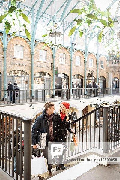 Junges Einkaufspaar auf der Treppe in Covent Garden  London  UK Junges Einkaufspaar auf der Treppe in Covent Garden, London, UK