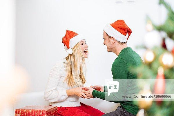 Junger Mann überreicht Weihnachtsgeschenk an glückliche Freundin Junger Mann überreicht Weihnachtsgeschenk an glückliche Freundin