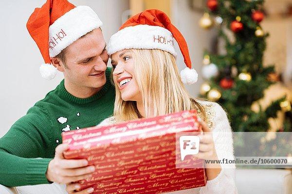 Romantisches junges Paar mit Weihnachtsgeschenk Romantisches junges Paar mit Weihnachtsgeschenk
