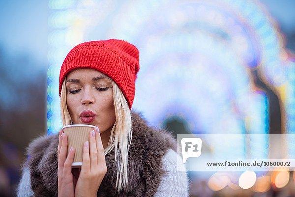Junge Frau beim Glühweinblasen beim Weihnachtsfest  Hyde Park  London  UK