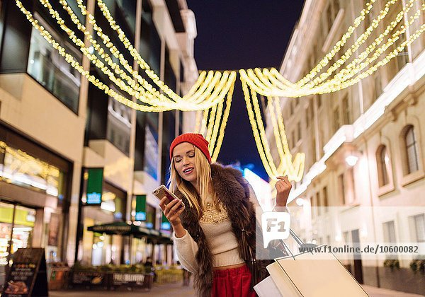 Young female shopper reading smartphone texts on street at xmas  London  UK