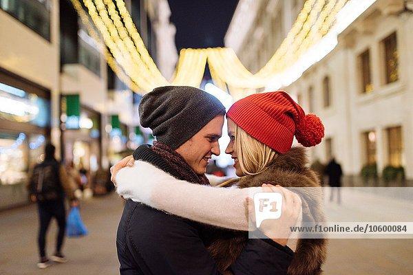 Romantisches junges Paar  das sich an Weihnachten auf der Straße umarmt  London  UK