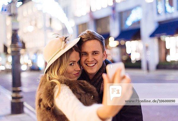 Junges Paar nimmt Smartphone Selfie an Weihnachten in der New Bond Street  London  UK Junges Paar nimmt Smartphone Selfie an Weihnachten in der New Bond Street, London, UK
