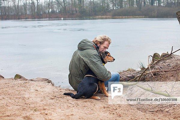 Erwachsener Mann umarmt Hund am Flussufer