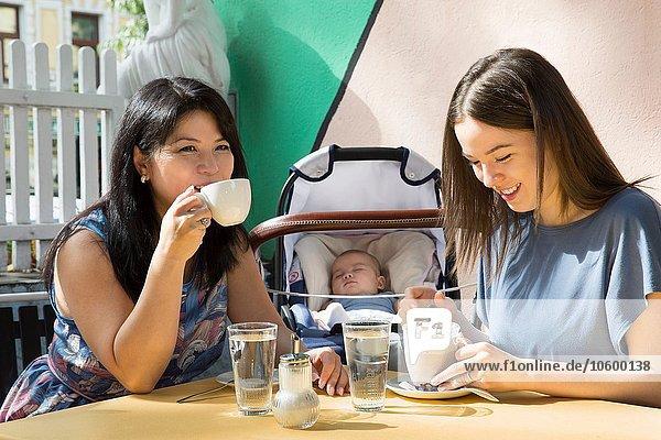 Junge Frau mit Mutter und Tochter beim Kaffeetrinken im Straßencafé
