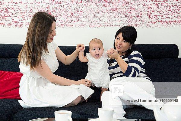 Reife Frau und Tochter beim Spielen mit dem Mädchen auf dem Sofa