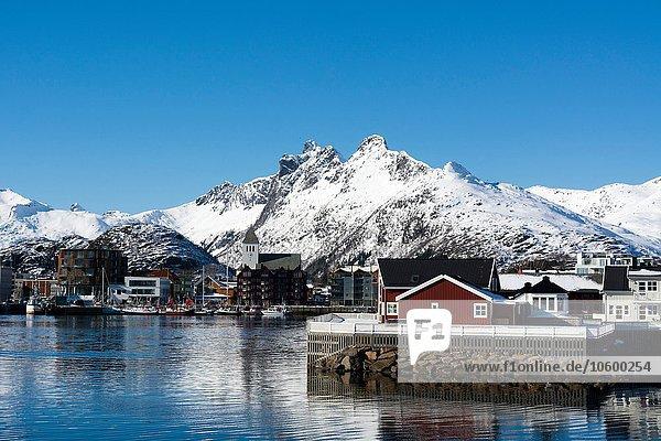 Blick auf Häuser am Wasser und schneebedeckte Berge  Svolvaer  Lofoten  Norwegen