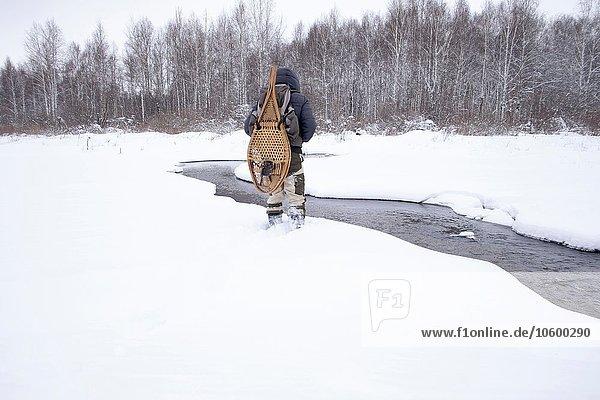 Rückansicht des erwachsenen Mannes im schneebedeckten Feld am Fluss mit traditionellen Schneeschuhen  Ural  Russland