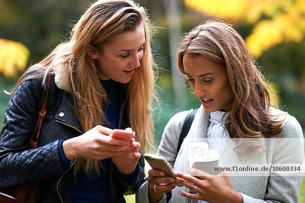 Two young female friends drinking coffee and reading smartphone texts in park