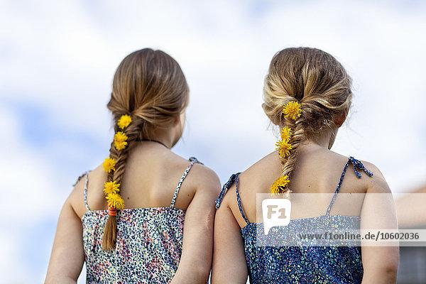 Girls with dandelion flower in braid