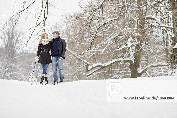 Couple walking dog through winter park