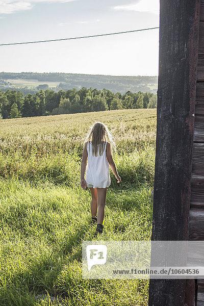 Girl walking near wooden house