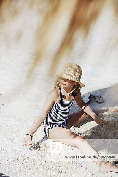 Girl sitting on sand