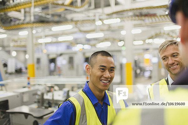 Arbeiter in reflektierender Kleidung sprechen in der Fabrik