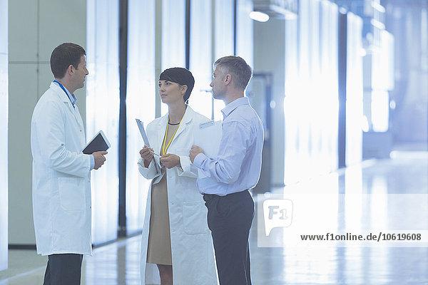 Wissenschaftler und Geschäftsleute sprechen im Fabrikkorridor