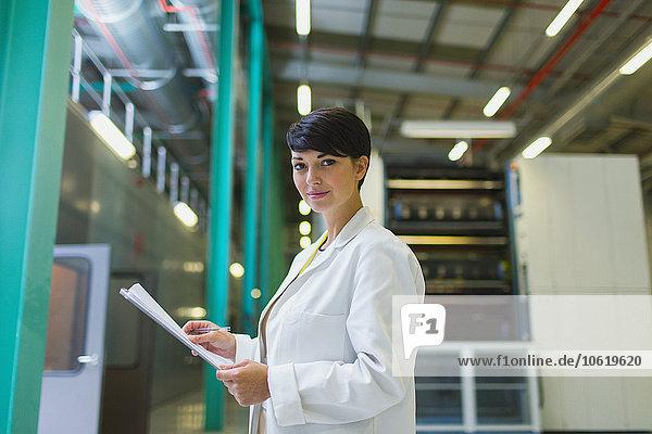 Porträt eines selbstbewussten Wissenschaftlers mit Papierkram in der Fabrik