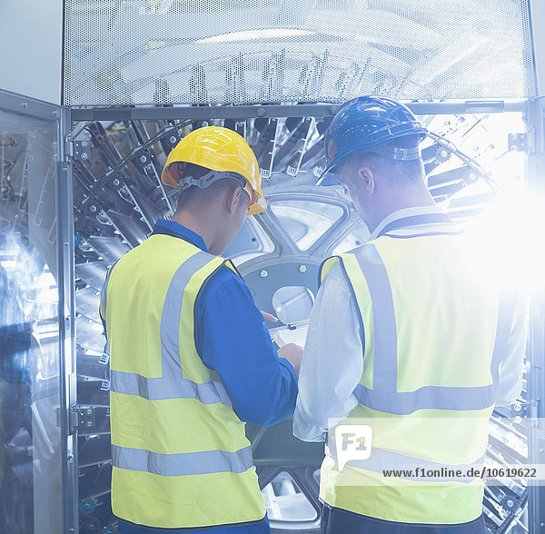 Mitarbeiter mit Klemmbrettprüfmaschinen in der Druckerei
