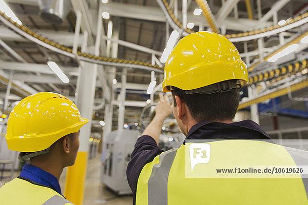 Arbeiter diskutieren über Druckmaschinen-Förderbänder über Kopf