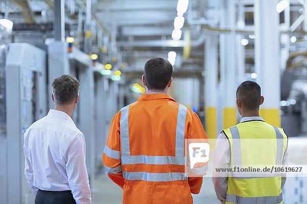 Arbeiter und Aufseher stehen im Fabrikkorridor