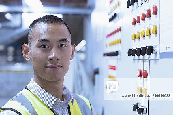 Porträt eines selbstbewussten Arbeiters am Bedienpult in der Fabrik