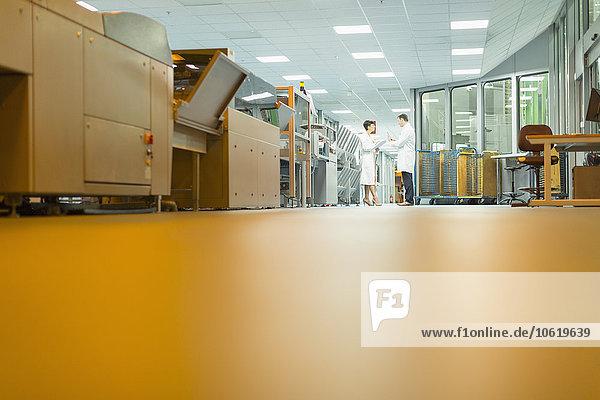 Arbeiter im Gespräch in der Nähe von Maschinen in der Druckerei