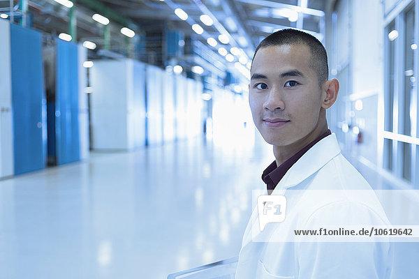 Porträt eines selbstbewussten Wissenschaftlers im Fabrikkorridor