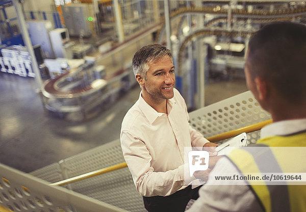 Vorgesetzter und Arbeiter beim Händeschütteln in der Fabrik