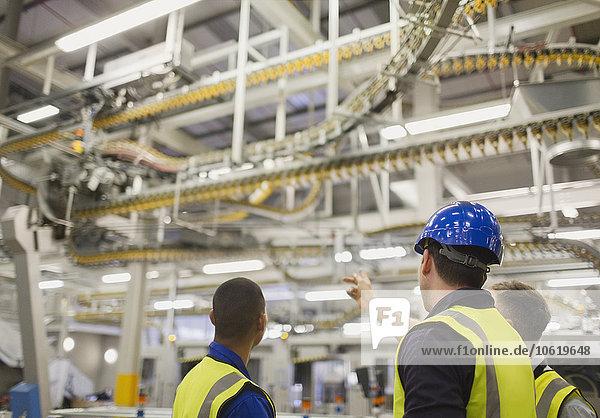 Arbeiter diskutieren über Förderbänder für Wickelmaschinen über Kopf