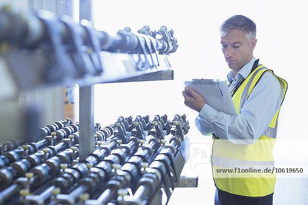 Ingenieur mit Zwischenablage zur Kontrolle des Förderbandes einer Druckmaschine