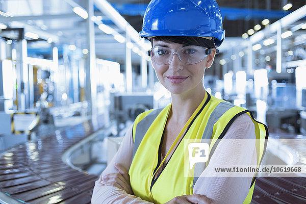 Porträt einer selbstbewussten Arbeiterin mit Schutzbrille und Schutzbrille in der Fabrik