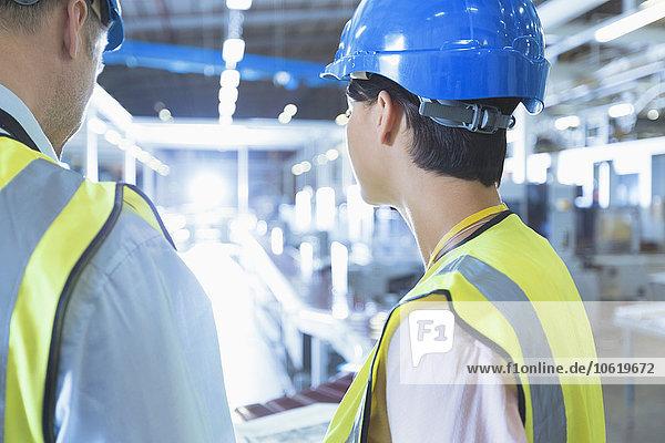 Arbeiter in reflektierender Kleidung und Schutzhelm in der Fabrik
