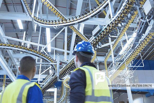 Arbeiter sehen sich die Förderbänder der Wickelmaschine an.