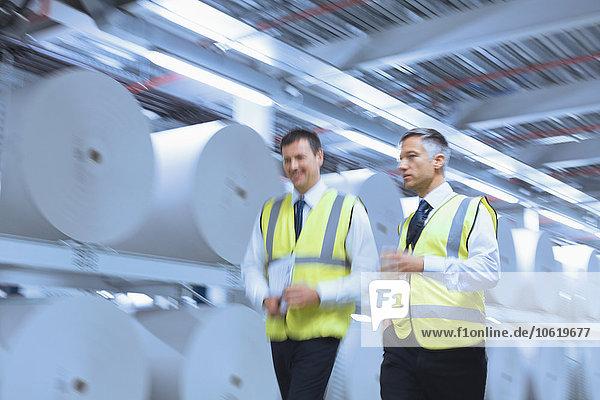 Geschäftsleute in reflektierender Kleidung, die in der Druckerei an großen Papierrollen entlanggehen