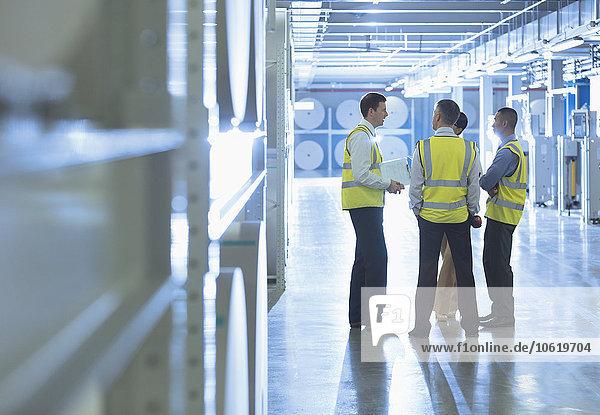Arbeiter reden im Fabrikkorridor