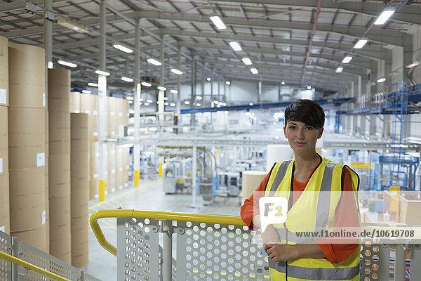 Porträt eines selbstbewussten Arbeiters auf der Plattform über der Fabrik