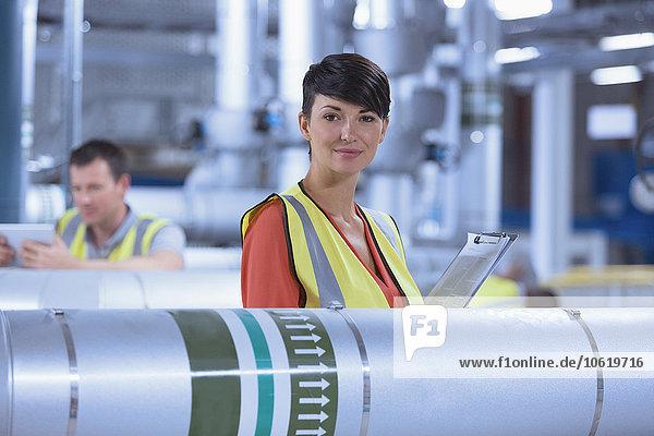 Porträt einer selbstbewussten Arbeiterin mit Zwischenablage in der Fabrik