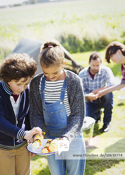 Geschwister schauen sich auf dem sonnigen Campingplatz Gemüse-Spieße an.