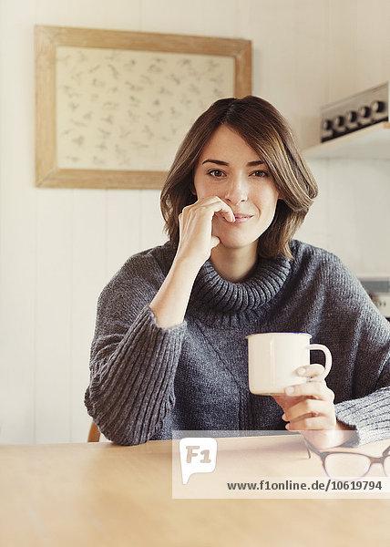 Portrait selbstbewusste brünette Frau beim Kaffeetrinken am Tisch